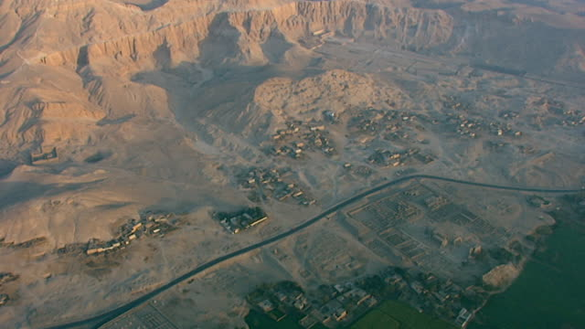 tilt-up from the west bank of the nile to the arid views of deir el bahari and the mortuary temple complex of hatshepsut. - tempio di hatshepsut video stock e b–roll