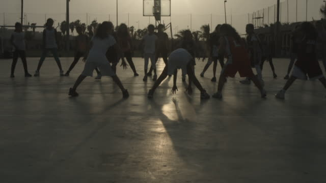 tilt-up of children participating in a calisthenics class at the jeddah-united sports grounds. - jiddah点の映像素材/bロール