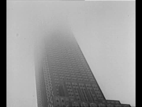 vídeos de stock, filmes e b-roll de tiltup shot empire state building with top shrouded in fog / tiltup shot smoke surrounds upper floors of empire state / people scurry on 34th street... - paramount building