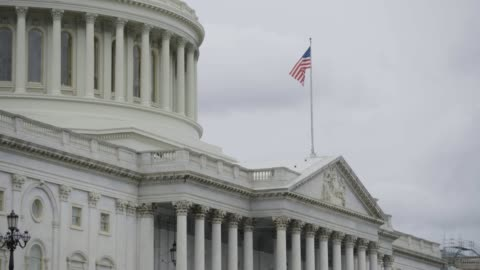 tilt-up shot from the us flag to the united states capitol dome - united states congress stock videos & royalty-free footage