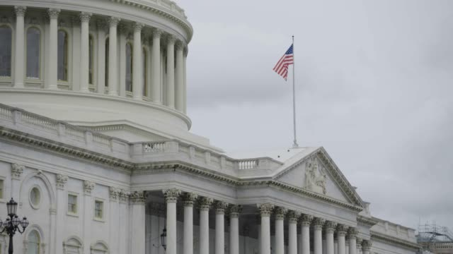 tilt-up shot from the us flag to the united states capitol dome - united states congress stock-videos und b-roll-filmmaterial