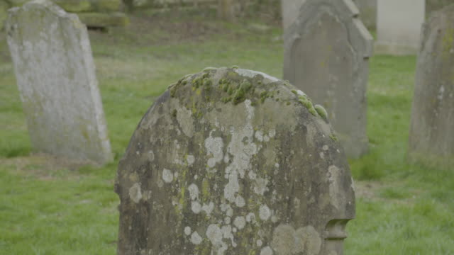 tilt-up shot of a mossy tombstone at the graveyard of the church of st mary the virgin in ashwell - cemetery stock videos & royalty-free footage
