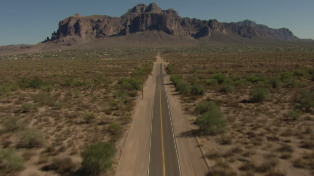 tilt-up shot of a road leading toward a barren mountain in arizona - shrubland stock videos & royalty-free footage