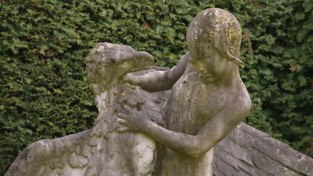 tilt-up shot of a sculpture of a child with an eagle at boughton house - stone object stock videos & royalty-free footage