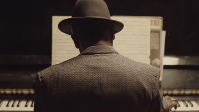 vídeos de stock e filmes b-roll de tilt-up shot of a senior african-american pianist playing the piano - bar clandestino
