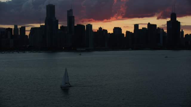 tilt-up shot of downtown chicago at sunset - lago michigan video stock e b–roll
