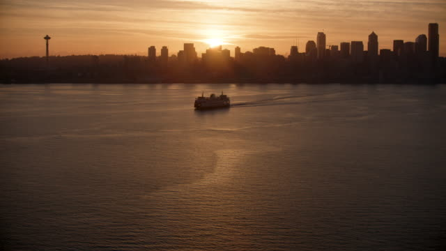 tilt-up shot of downtown seattle with the elliott bay in the foreground at sunrise - washington state stock videos & royalty-free footage