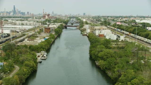 tilt-up shot of the chicago sanitary and ship canal with downtown chicago in the background - chicago river stock videos & royalty-free footage