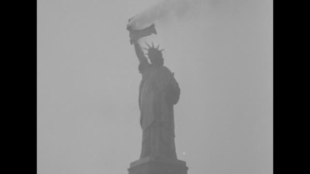 tiltup shot the statue of liberty stands with her torch smoking as an american flag waves / note exact day not known - statue of liberty new york city stock videos & royalty-free footage