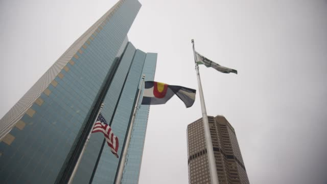 stockvideo's en b-roll-footage met tilt-up to american and colorado flags flying in downtown denver - nationale vlag
