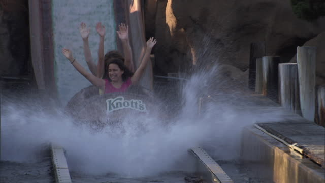 timber mountain log ride at knott's berry farm theme park, teens laughing as they descend into water - fahrzeug fahren stock-videos und b-roll-filmmaterial