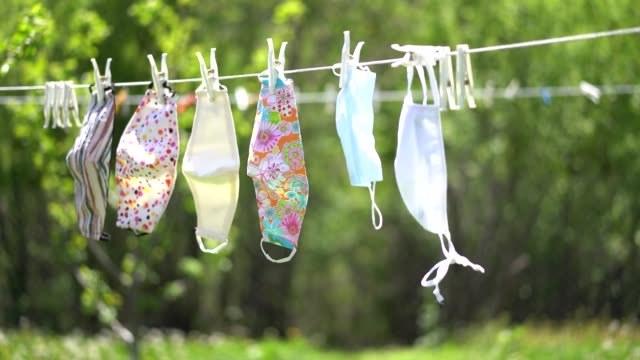 time for new normality: face masks on the line after washing. no need after the pandemic. - convalescenza video stock e b–roll