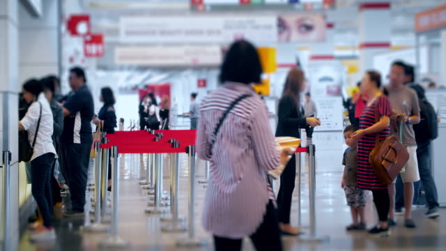 4k time lapse 4096x2160 : next in line , the crowd at airport passengers check in at ticket counter with prores 422hq (blur content).many people in shopping mall in hong kong - ticket stock videos & royalty-free footage