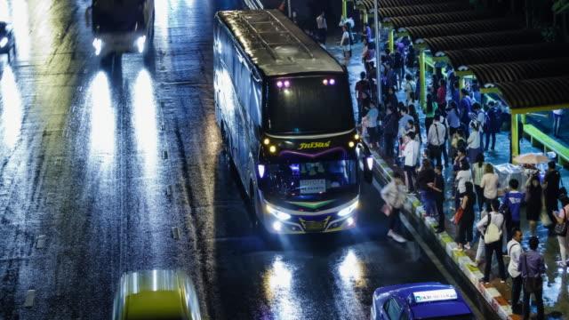 vídeos de stock, filmes e b-roll de lapso de tempo de 4k 4096 x 2160: pessoas esperar e continuar a cidade à noite de ônibus - estrada com carros - - closeup - ônibus