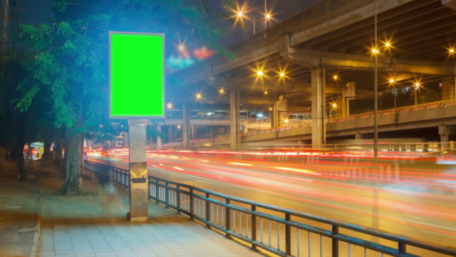 4k time lapse 4096x2160 : the traffic motion and green billboard with prores 422hq (blur content). - tabellone video stock e b–roll