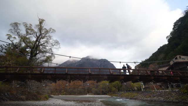 vídeos de stock, filmes e b-roll de tempo lapso 4k kamikoshi mountain view com ponte de kappa e pessoas andando na província de nagano nevoeiro, japão - estampa de folha