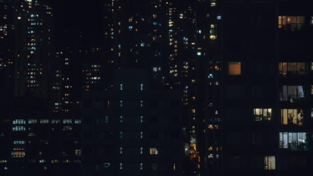 tidsfördröjning 4k upplösning fönster ljus av bostadshus område på natten. - fönsterrad bildbanksvideor och videomaterial från bakom kulisserna