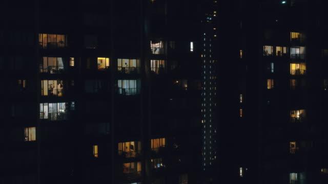 time lapse 4k risoluzione finestre luce della zona dell'edificio residenziale di notte. - appartamento video stock e b–roll