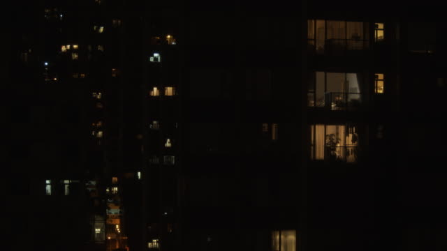 time lapse 4k resolution windows light of residential building area at night. - blinking stock videos & royalty-free footage