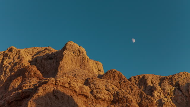 time lapse a partial moon moves across the sky as the sun sets on a rugged rocky terrain. - badlands national park video stock e b–roll