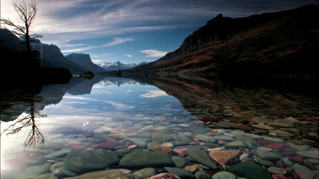 time lapse aerial over colored rocks in lake at foot of Rocky Mts / Glacier National Park, Montana