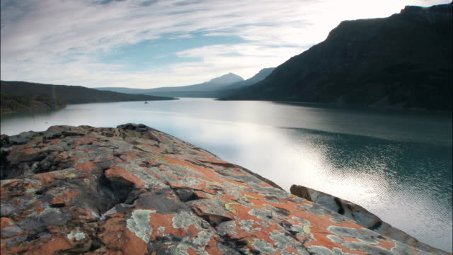 time lapse aerial over lichen-covered rocks towards lake at foot of rocky mts / glacier nat'l park, montana - 崖点の映像素材/bロール