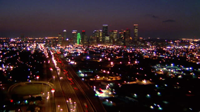 Time lapse aerial point of view over Houston skyline at night with traffic on highways and streets / Texas