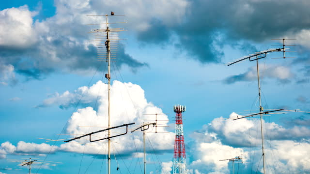 time lapse : aerial television antenna with cloud moving and blue sky - television aerial stock videos and b-roll footage
