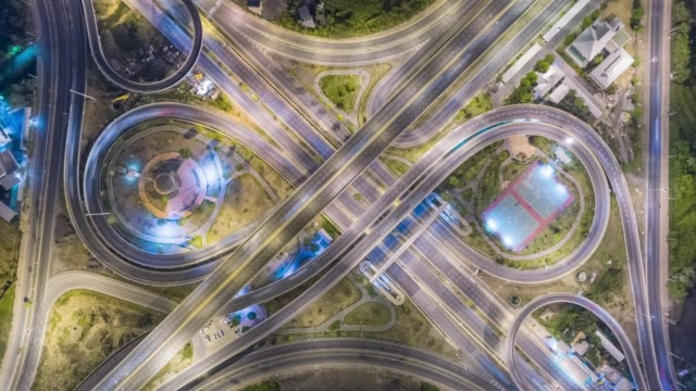 vídeos de stock, filmes e b-roll de 4k time lapse : aerial top view highway road roundabout or intersection, circle at night for transportation, distribution or futuristic concept background. - junção de rua ou estrada