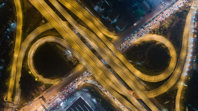 4k time lapse : aerial top view highway road roundabout or intersection, circle at night for transportation, distribution or futuristic background. - straßenüberführung stock-videos und b-roll-filmmaterial
