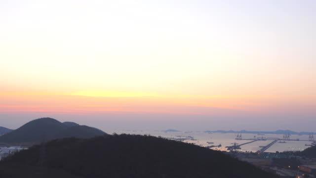 vidéos et rushes de laps de temps: vue aérienne, cargo ship au coucher du soleil dans le port de long beach - soulever
