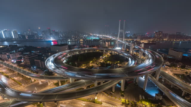 time lapse- aerial view of busy road intersection in shanghai (ws ha panning) - 螺旋形点の映像素材/bロール