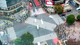 Time lapse aerial view of pedestrians walking across with crowded traffic at Shibuya crossing square