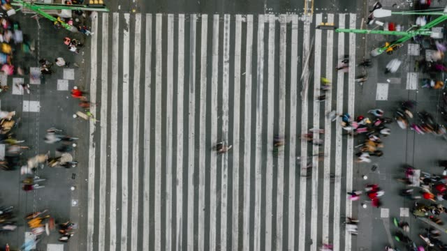 time lapse aerial view of pedestrians walking across with crowded traffic. - pedestrian crossing stock videos & royalty-free footage