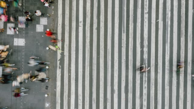time lapse aerial view of pedestrians walking across with crowded traffic. - zebra crossing stock videos & royalty-free footage