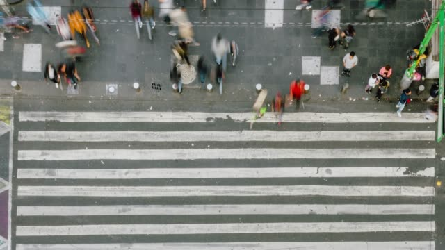 time lapse aerial view of pedestrians walking across with crowded traffic. - crossroad stock videos & royalty-free footage