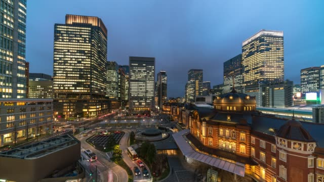 4k time lapse aerial view of tokyo station and marunouchi with various building cityscape and traffic road at sunset time in tokyo city, japan. japanese culture and transportation concept - marunouchi stock videos & royalty-free footage