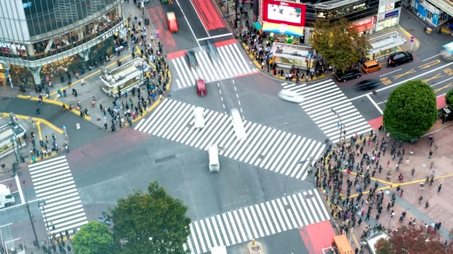 vídeos de stock, filmes e b-roll de lapso de tempo vista aérea zoom de pedestres atravessando com tráfego lotado na praça de cruzamento de shibuya - cruzando