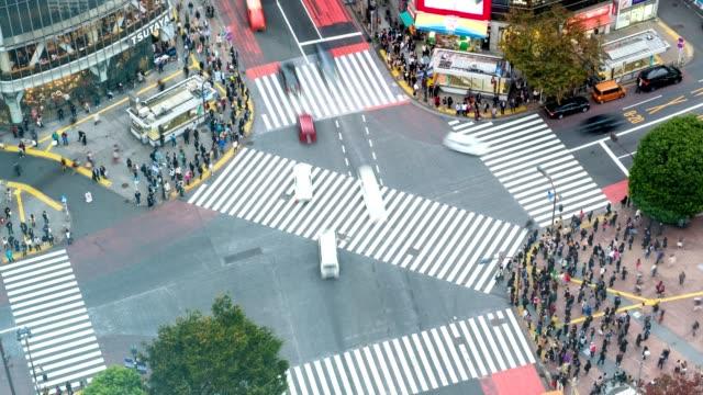 vídeos de stock, filmes e b-roll de zoom de vista aérea de lapso de tempo fora de pedestres atravessando com tráfego lotado na praça de cruzamento de shibuya - exposição longa