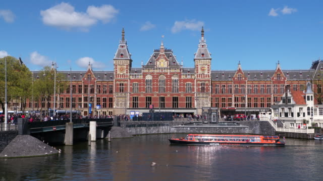 Time Lapse. Amsterdam central station and boats on canal. Amsterdam, North Holland, Netherlands