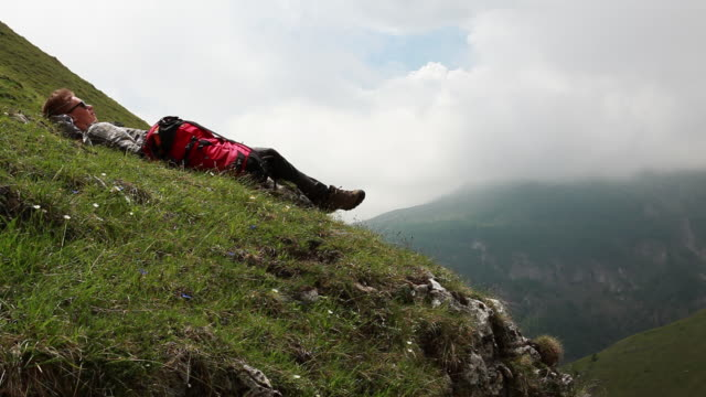 time lapse as teenage hiker rests in meadow, clouds move past - one teenage boy only stock videos & royalty-free footage