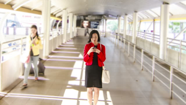 time lapse : Asian businesswoman using smartphone while travelling at urban scene