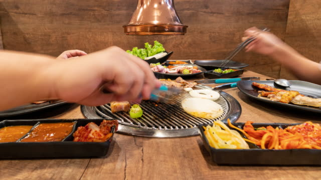 zeitraffer: asiaten grillen bbq in koreanischen restaurants. lebensmittelkonzept - korea stock-videos und b-roll-filmmaterial