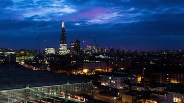A time lapse at dawn of the Shard (London, UK) featuring lights going out in the surrounding buildings as the sky changes from dark to a vivid blue