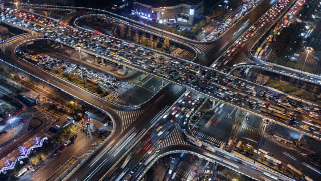 tl/ time lapse, at night, of busy road intersection in beijing's financial district, with traffic and commuters at rush hour - beijing stock videos & royalty-free footage