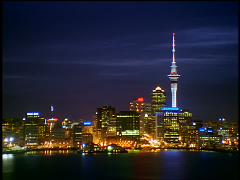 time lapse Auckland city skyline + boats in Waitemata Harbor at night / Auckland, New Zealand