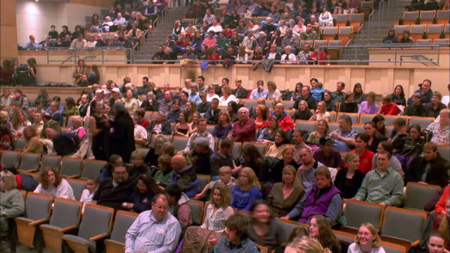 Time lapse audience taking seats in theater and watching performance / Colorado