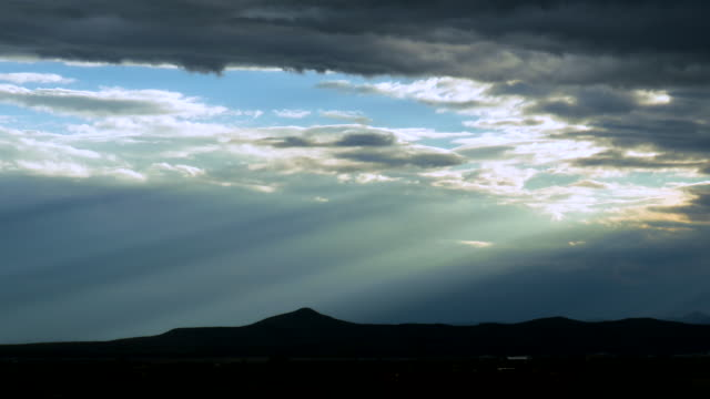 Time lapse beams of sunlight clouds passing New Mexico mountains