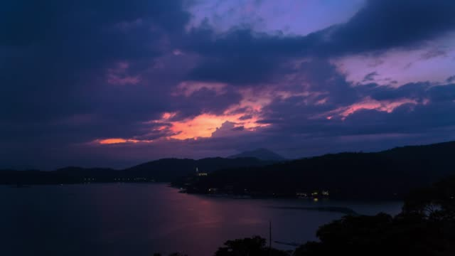 4k time lapse: beautiful cloudscape of sun moon lake at the sunset, taiwan, tilt up shot - sun moon lake stock videos and b-roll footage