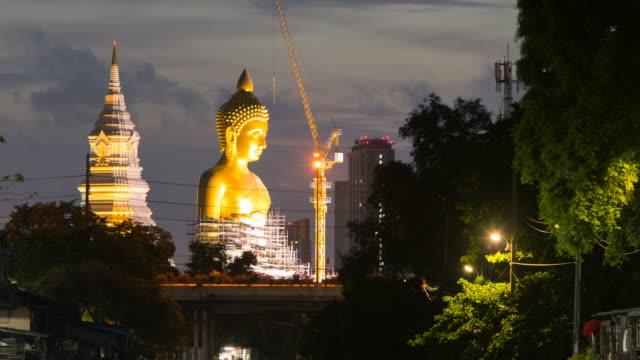 time lapse grande statua di buddha d'oro in costruzione al tempio wat paknam bhasicharoen al tramonto, a bangkok, thailandia; zoom indietro movimento - bangkok video stock e b–roll